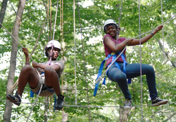 Two scholars from the Class of 2012 performing a challenging rope course activity