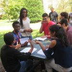Group of scholars from the Class of 2020 having a small group discussion outdoors on a sunny day during their Personal Development course.